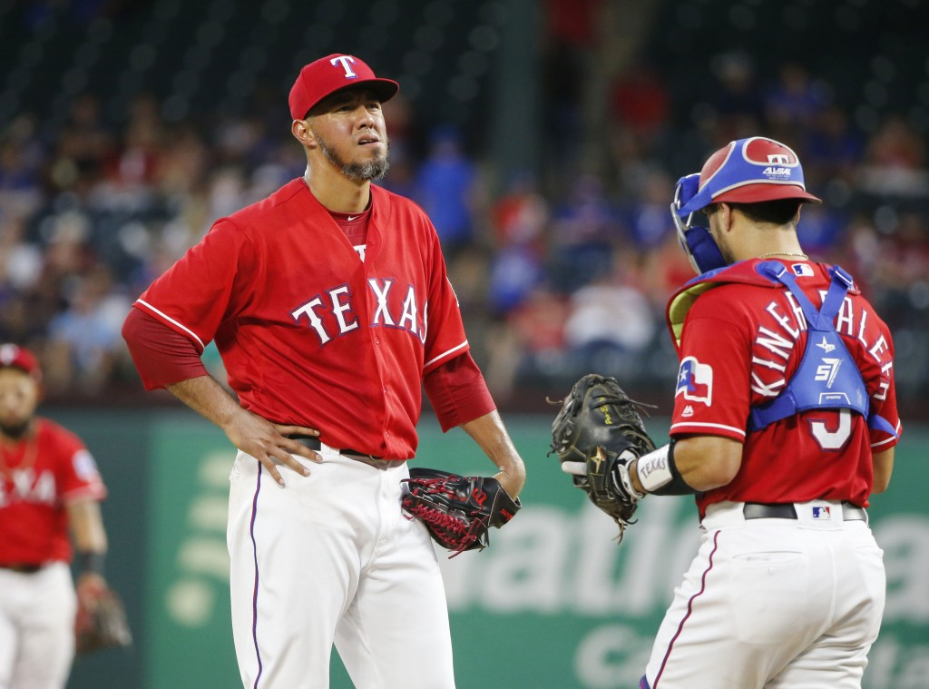 Texas Rangers starting pitcher Yovani Gallardo (49) reacts as catcher Isiah Kiner-Falefa (9), walks to the mound during a pitching change in the fourt...