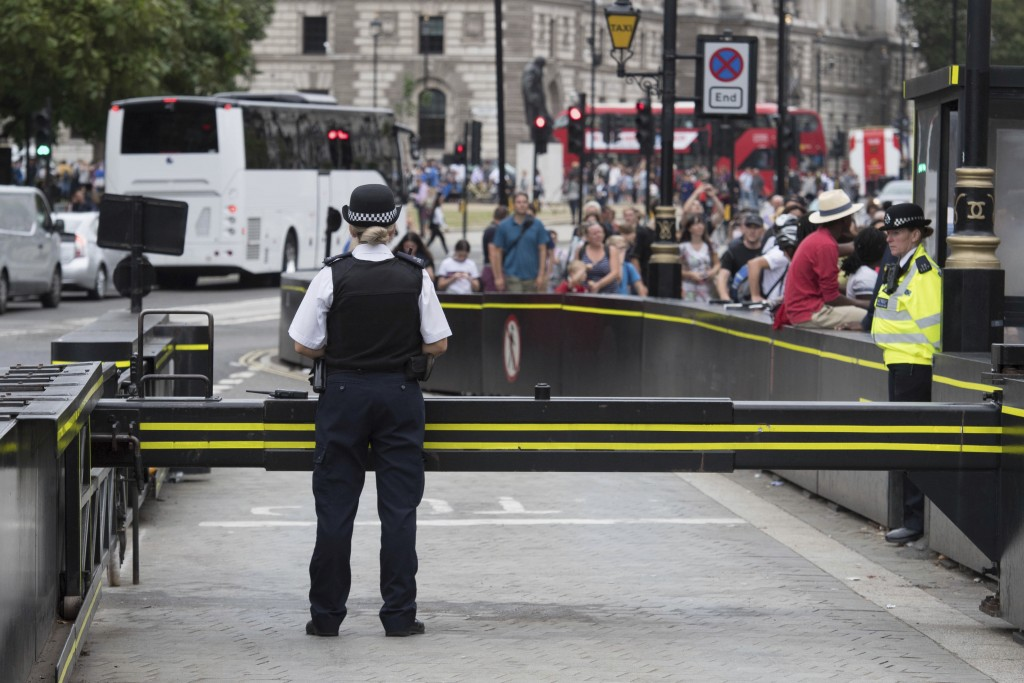 The area is packed with tourists as police secure the scene near a road barrier outside the Houses of Parliament in London, the day after a suspected ...