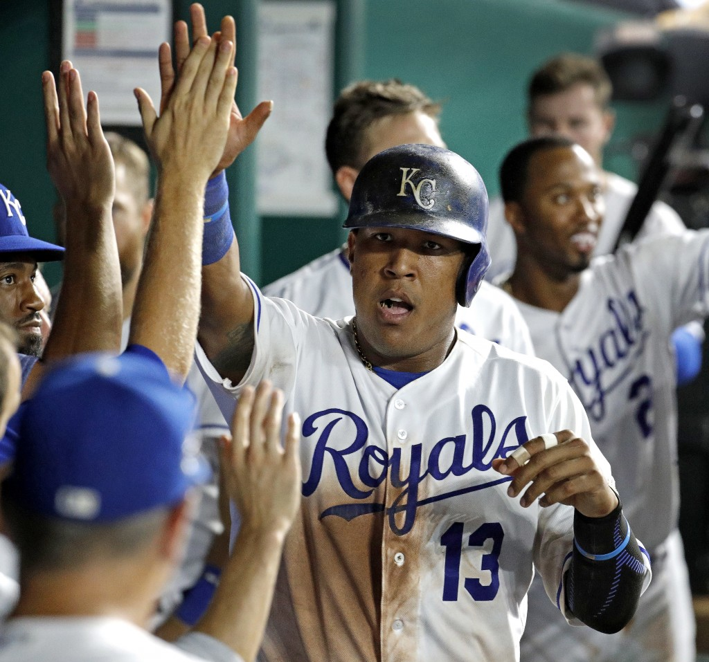 Kansas City Royals' Salvador Perez celebrates in the dugout after scoring on a double by Jorge Bonifacio during the seventh inning of a baseball game ...