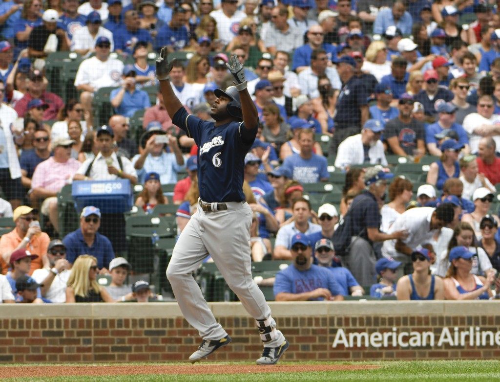 Milwaukee Brewers' Lorenzo Cain gestures as he's about to cross home plate after hitting a home run against the Chicago Cubs during the first inning o...