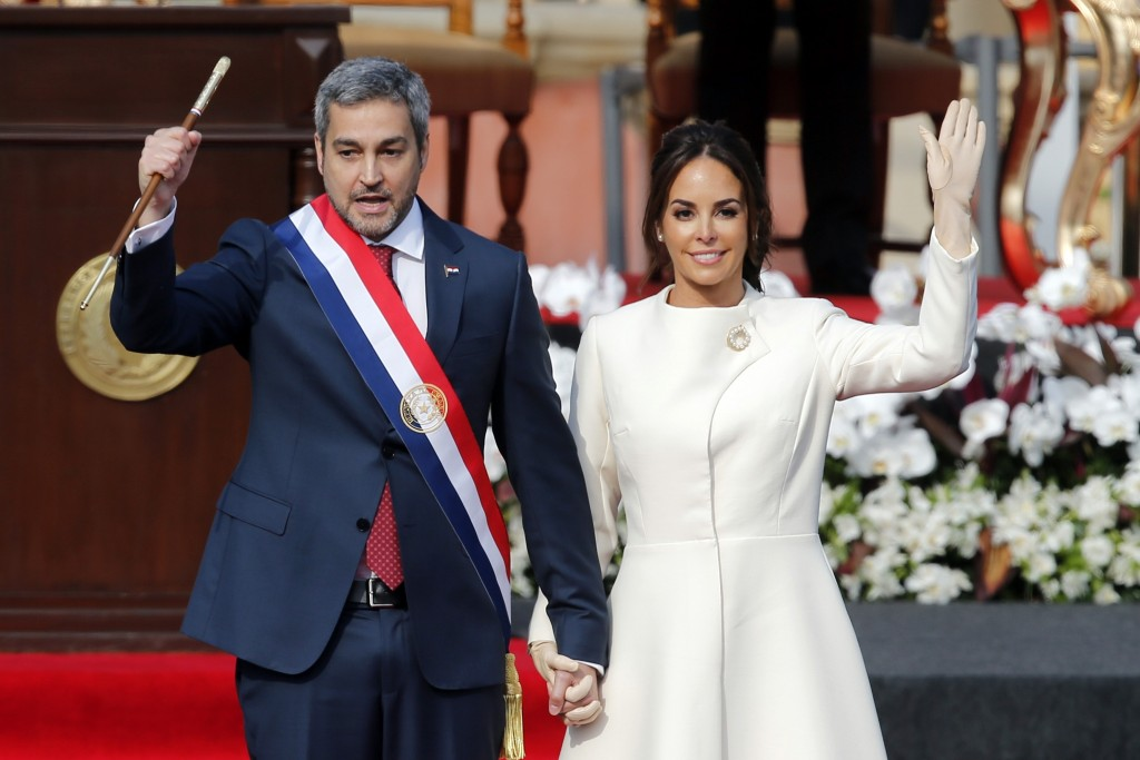 """Paraguay's new President Mario Abdo Benitez, flanked by his wife Silvana Lopez, acknowledges the crowd after taking the oath of office at """"Lopez Palac..."""