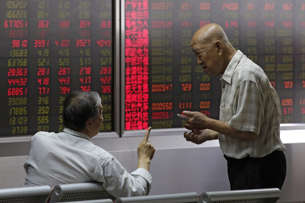 People chat as they monitor stock prices at a brokerage house in Beijing, Thursday, Aug. 16, 2018. Asian shares are falling as investors fret over slo...