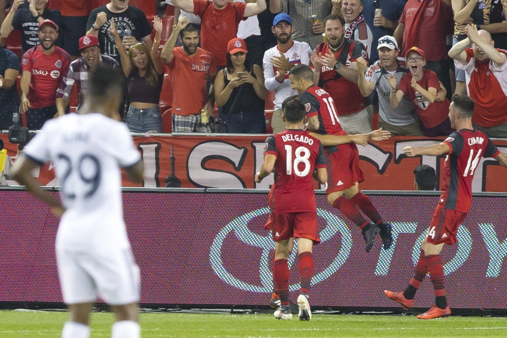 Toronto FC's Sebastian Giovinco, center, celebrates scoring against the Vancouver Whitecaps during the first half in the second leg of the Canadian so...