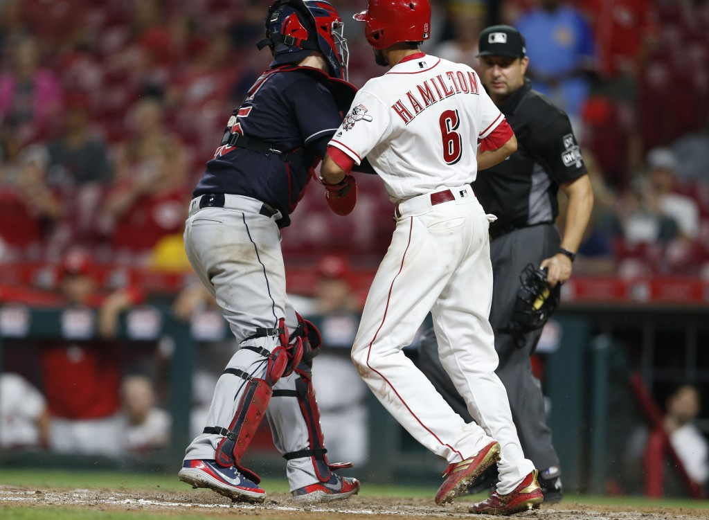 Cincinnati Reds' Billy Hamilton (6) is tagged out at the plate by Cleveland Indians catcher Roberto Perez, left, while trying to score on a ground bal...