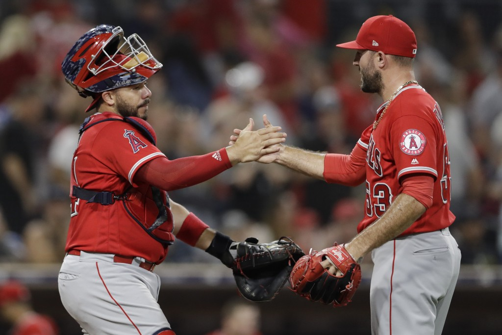 Los Angeles Angels catcher Rene Rivera, left, celebrates with relief pitcher Blake Parker after the Angeles defeated the San Diego Padres 3-2 in a bas...