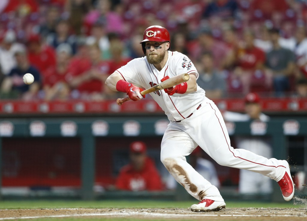 Cincinnati Reds' Tucker Barnhart bunts for a single off Cleveland Indians starting pitcher Shane Bieber during the third inning of a baseball game Wed...