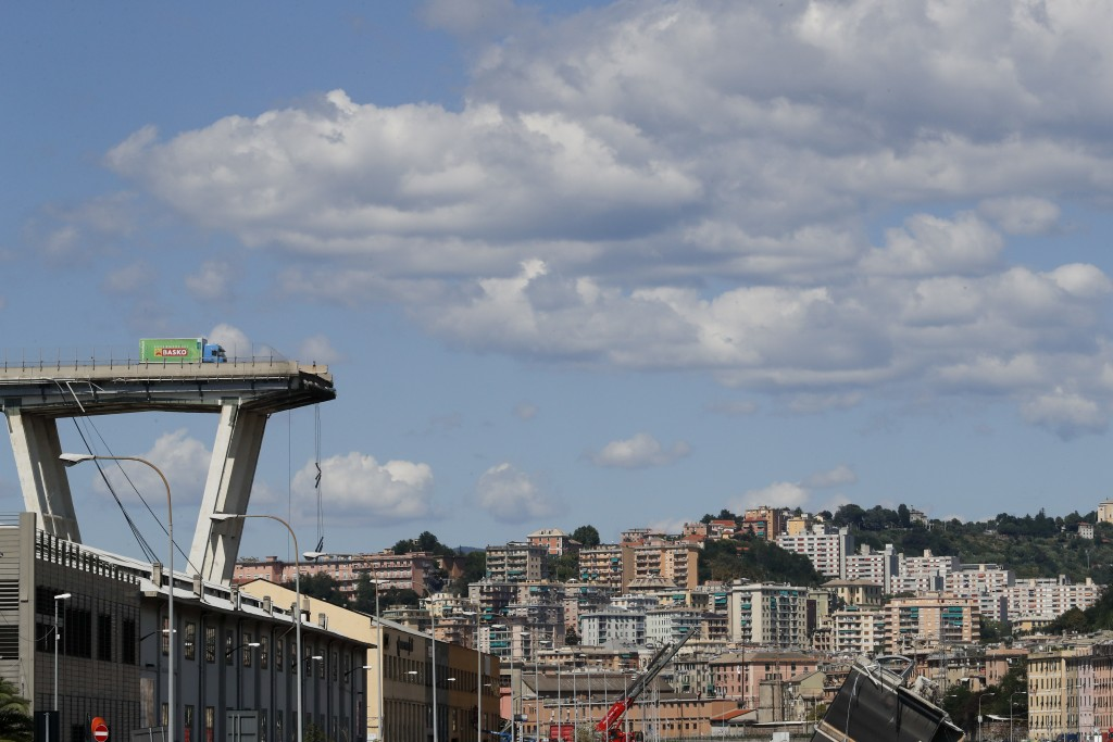 A truck perches on the edge of the Morandi highway bridge that collapsed in Genoa, northern Italy, Wednesday, Aug. 15, 2018. A large section of the br...