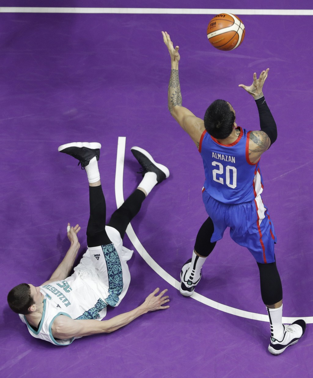 Philippines' Raymond Almazan, right, controls the ball against Kazakhstan Maxim Marchuck during their men's basketball match at the 18th Asian Games i...