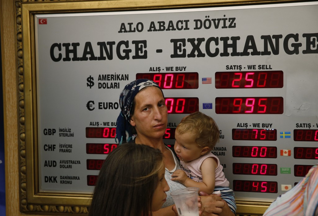 People wait at a currency exchange shop in Istanbul, Wednesday, Aug. 15, 2018. The Turkish lira has nosedived in value in the past week, but some Turk...