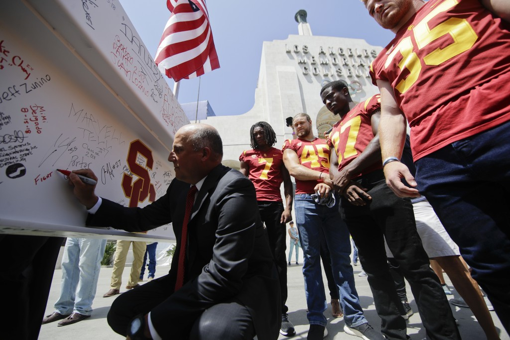 University of Southern California head coach Clay Helton signs the final beam, as players look on, in front of the Los Angeles Memorial Coliseum in Lo...