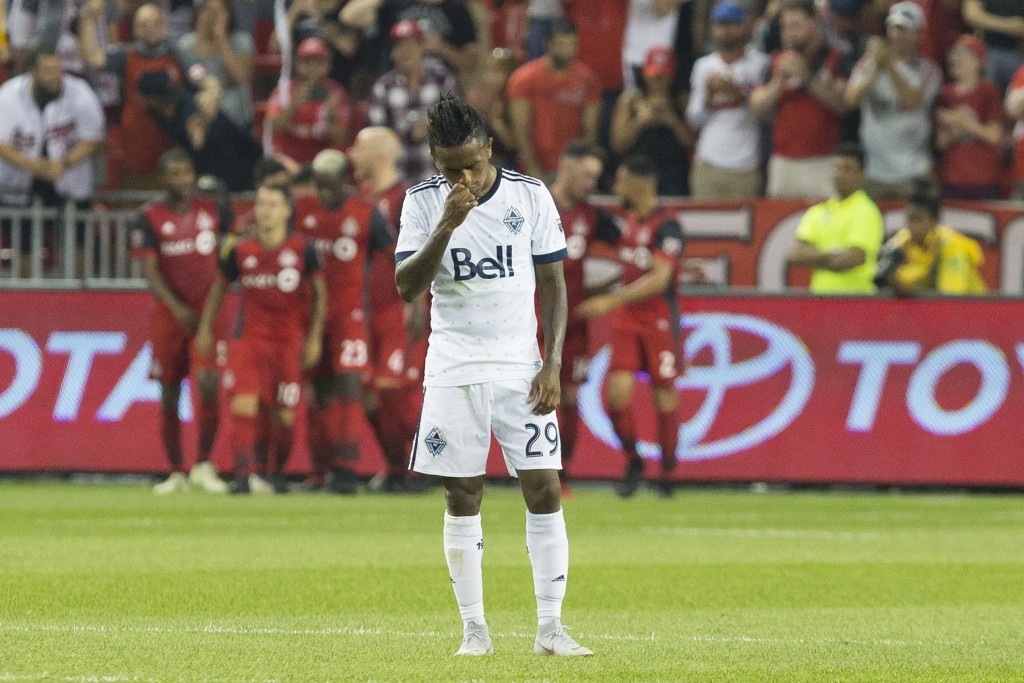 Vancouver Whitecaps' Yordi Reyna reacts as Toronto FC's Sebastian Giovinco, rear left, and teammates celebrate a goal during the first half in the sec...