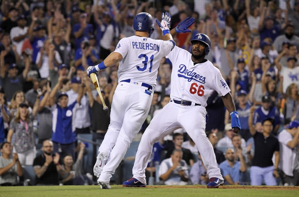 Los Angeles Dodgers' Yasiel Puig, right, celebrates with Joc Pederson afters scoring on a sacrifice by Pederson during the sixth inning against the Sa...