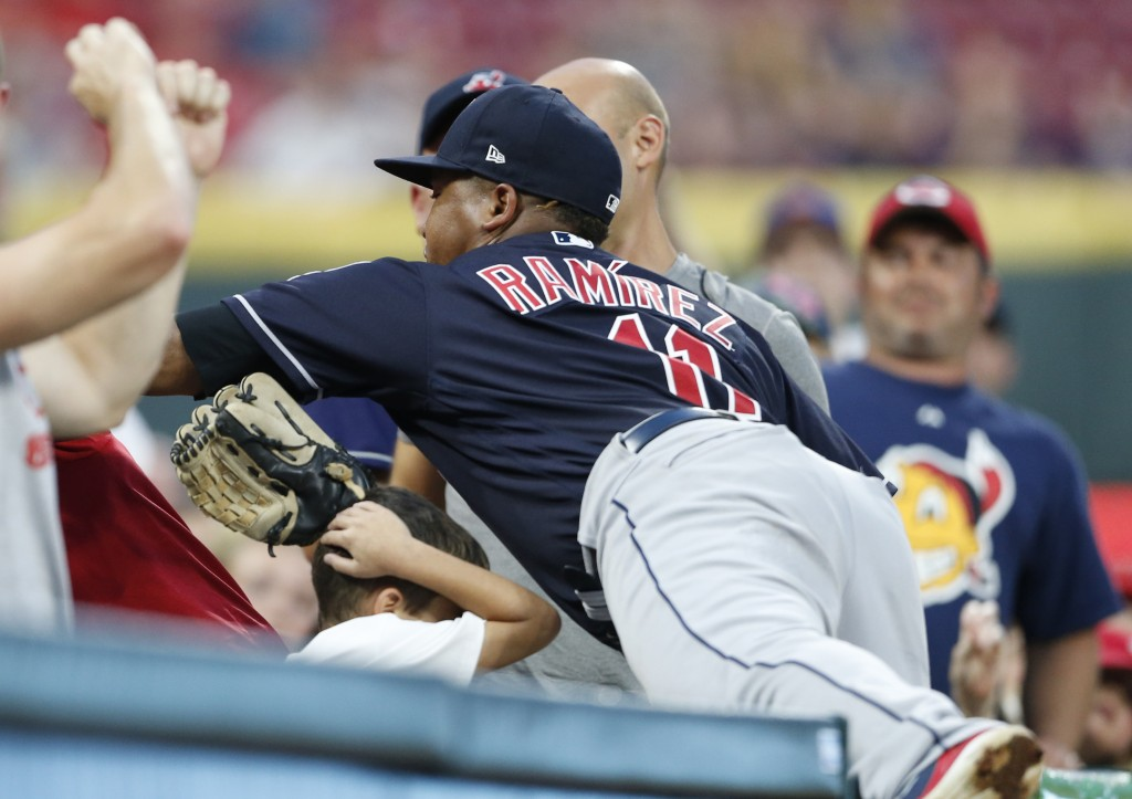 A young fan ducks as Cleveland Indians third baseman Jose Ramirez attempts to catch a foul ball hit by Cincinnati Reds' Preston Tucker during the thir...