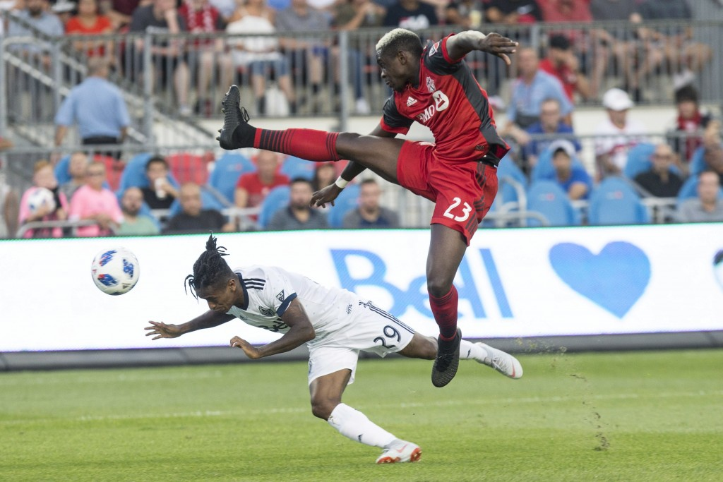 Vancouver Whitecaps forward Yordi Reyna, left, dives to get a header in front of Toronto FC defender Chris Mavinga during the first half in the second...