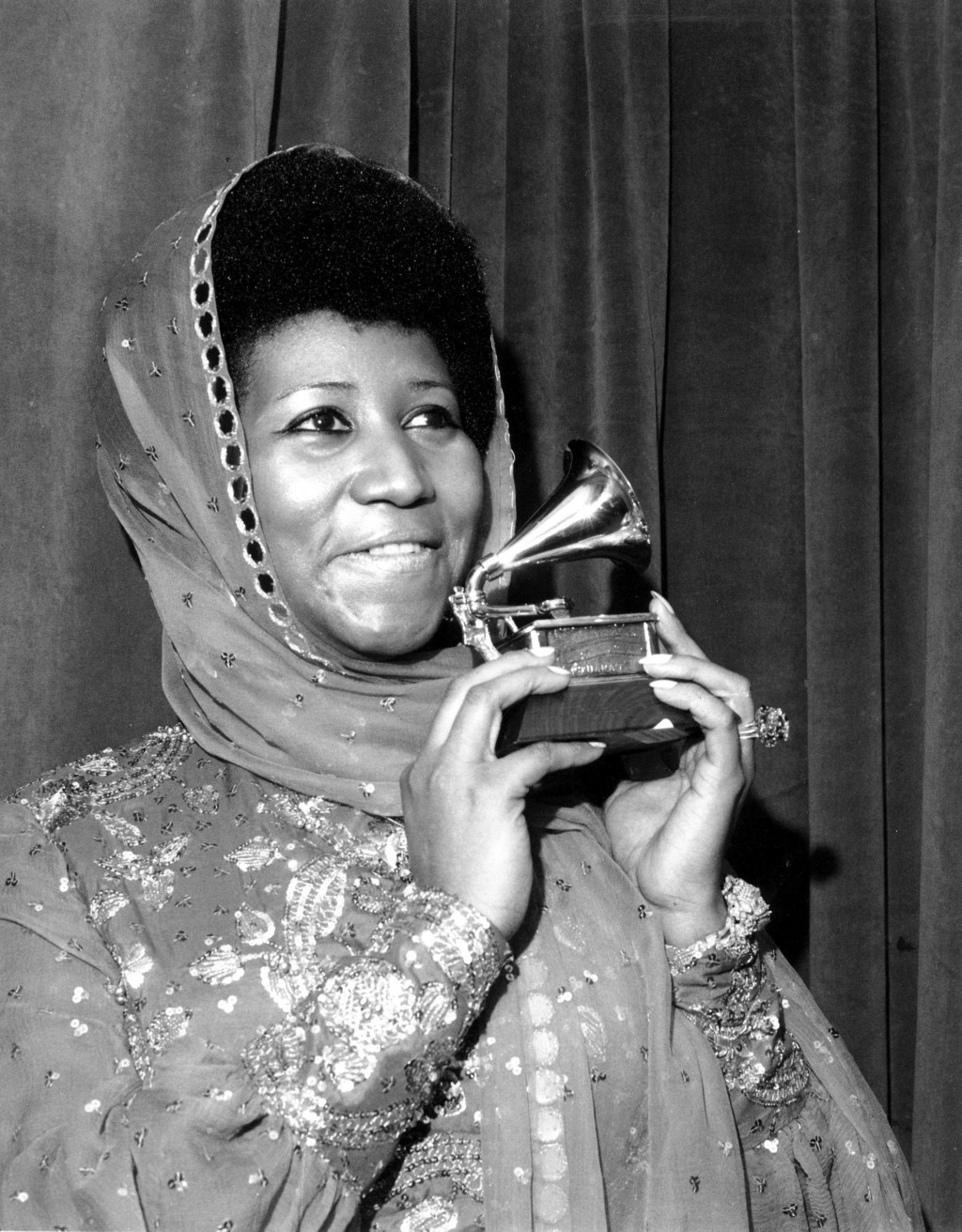 """FILE - In this March 3, 1975 file photo, singer Aretha Franklin poses with her Grammy Award for for best female R&B vocal performance for """"Ain't Nothi..."""