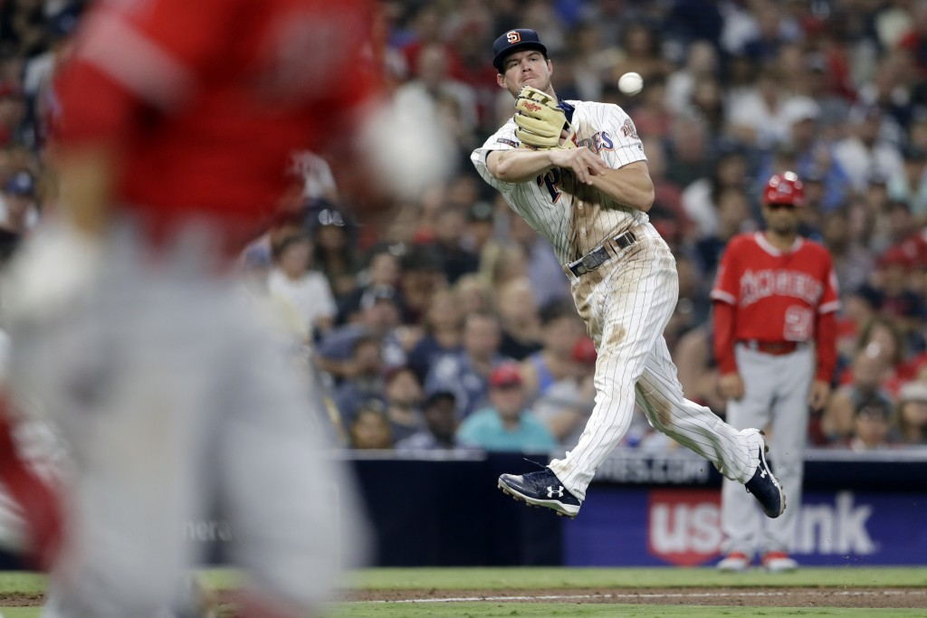 San Diego Padres third baseman Wil Myers, right, overthrows first base as Los Angeles Angels' David Fletcher, left, arrives with a single at first dur...