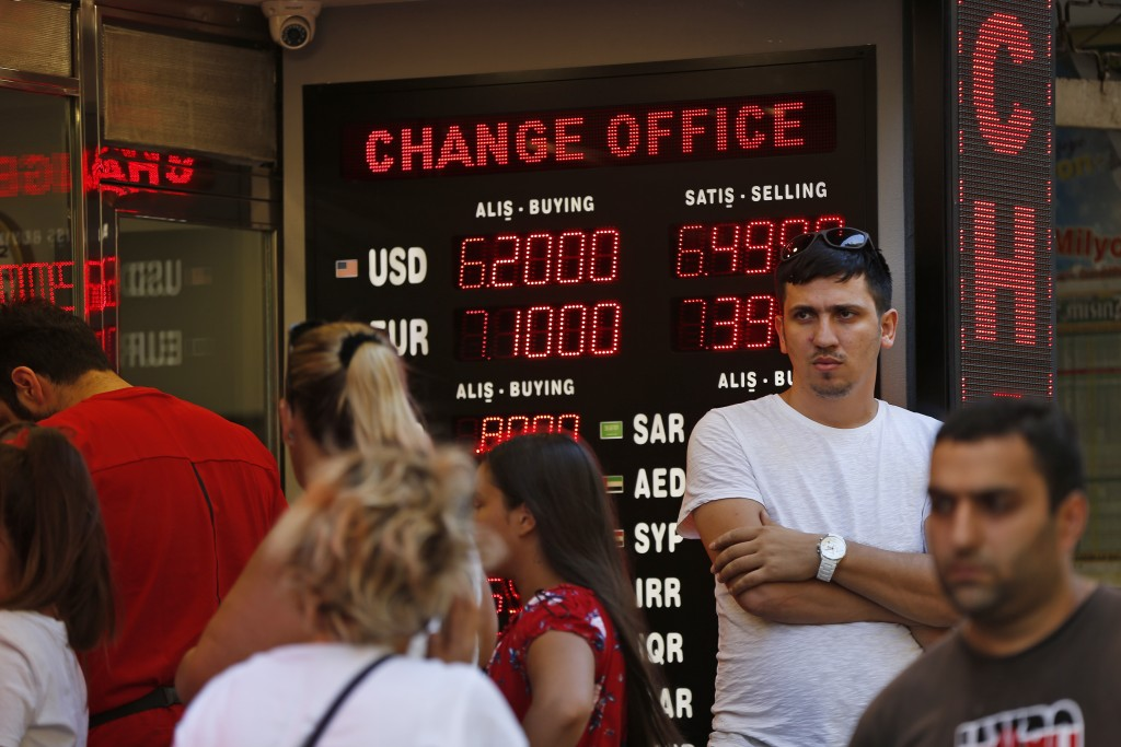 FILE- In this Tuesday, Aug. 14, 2018, file photo people line up at a currency exchange shop in Istanbul. Investors have been pulling out of Turkey's m...