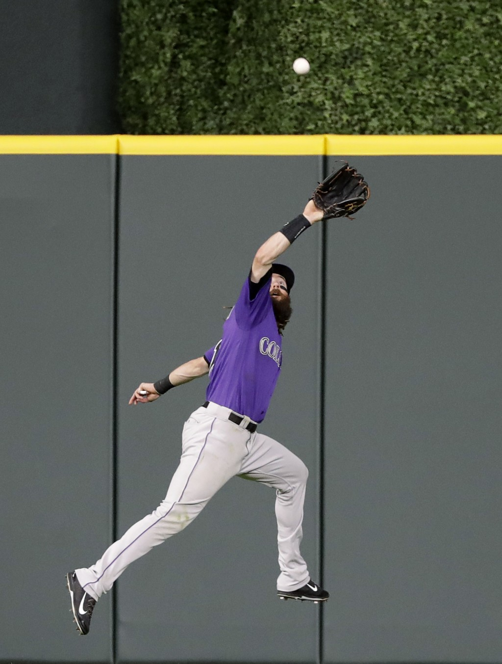 Colorado Rockies center fielder Charlie Blackmon leaps to make the catch on an RBI sacrifice fly by Houston Astros' Alex Bregman during the second inn...