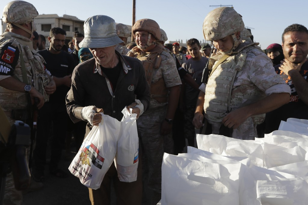 Local residents receive humanitarian aid from the Russian military in the town of Rastan, Syria, Wednesday, Aug. 15, 2018. The Russian Defense Ministr...