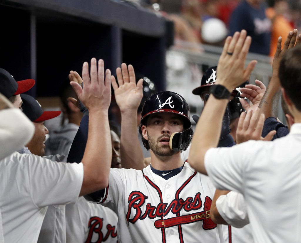 Atlanta Braves' Dansby Swanson is congratulated in the dugout after hitting a two-run home run during the fourth inning against the Miami Marlins in a...