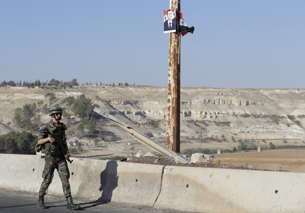 A Syrian army soldier patrols on the bridge in the town of Rastan, Syria, Wednesday, Aug. 15, 2018. The Russian Defense Ministry said it is coordinati...