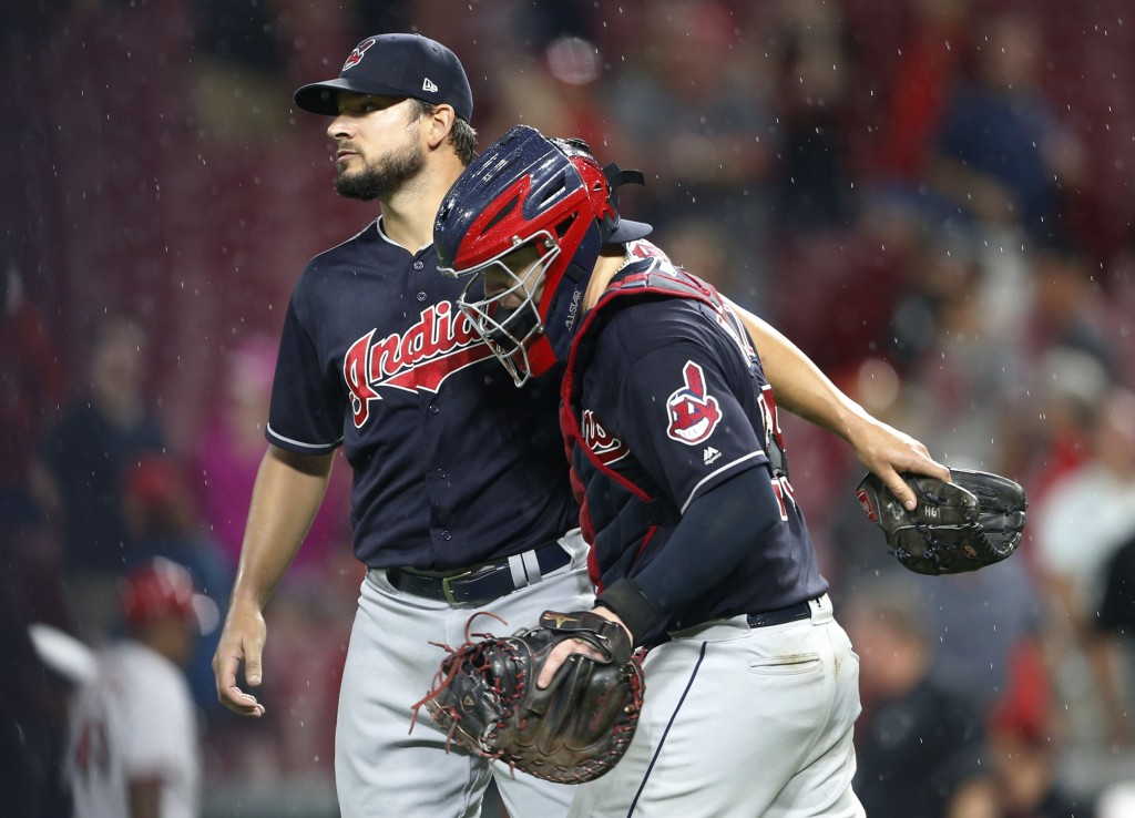 Cleveland Indians relief pitcher Brad Hand, left, and catcher Roberto Perez celebrate the team's 4-3 win over the Cincinnati Reds in a baseball game W...