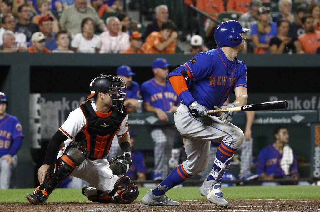 New York Mets' Brandon Nimmo watches his two-run triple in front of Baltimore Orioles catcher Austin Wynns during the sixth inning of a baseball game ...