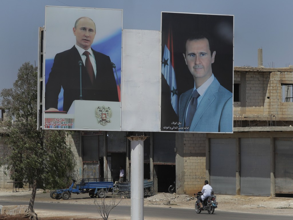 A local resident rides his motorcycle near portraits of Syrian President Bashar al-Asad, right, and Russian President Vladimir Putin in the town of Ra...