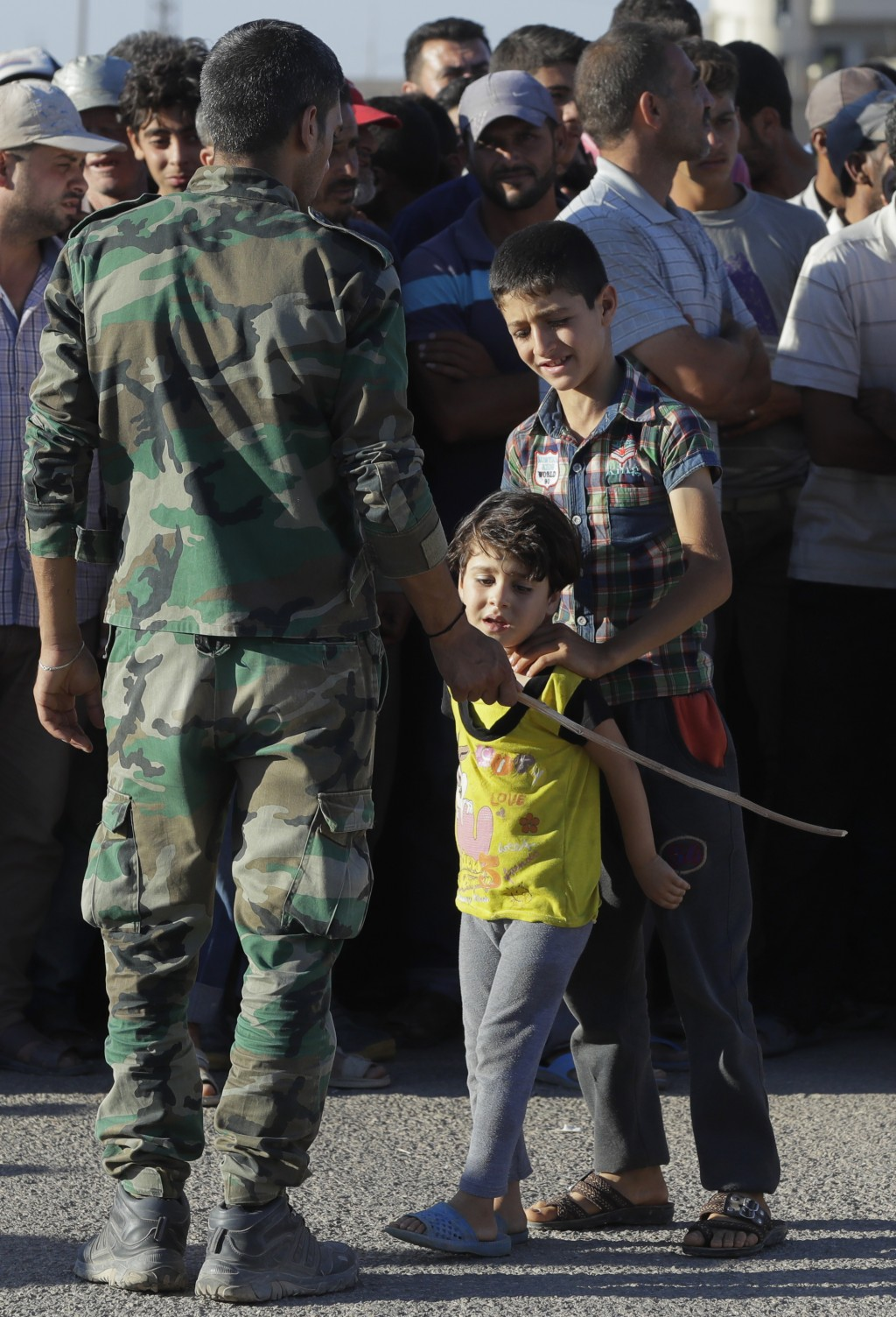 A soldier of Syrian army blocks a way for local children during distribution of humanitarian aid from the Russian military in the town of Rastan, Syri...