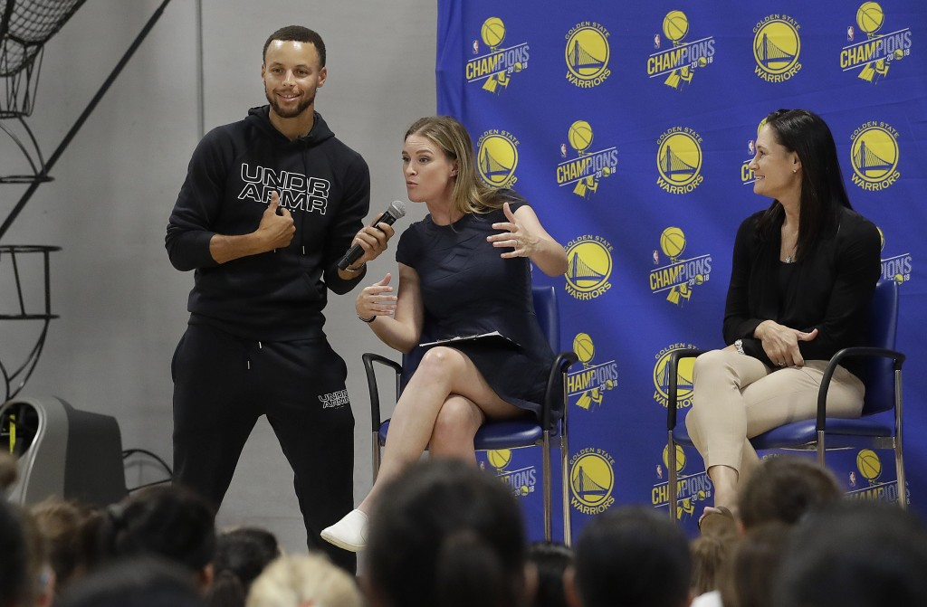 Golden State Warriors' Stephen Curry, from left, holds a microphone for broadcaster Kerith Burke as Jennifer Azzi listens as they speak to basketball ...
