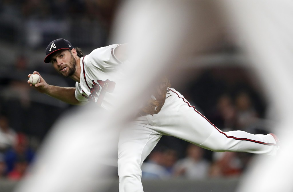 Atlanta Braves third baseman Charlie Culberson (16) is framed by first baseman Freddie Freeman as he throws out Miami Marlins' Austin Dean after bare-...