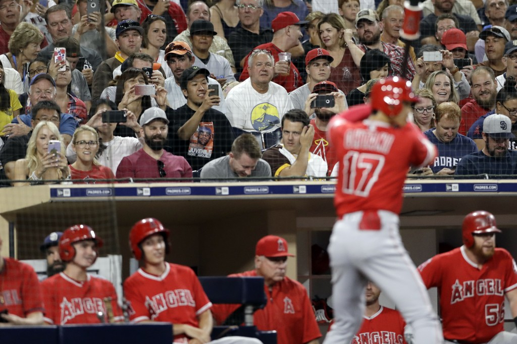 Fans record Los Angeles Angels' Shohei Ohtani, of Japan, as he waits on deck to bat during the ninth inning of the team's baseball game against the Sa...