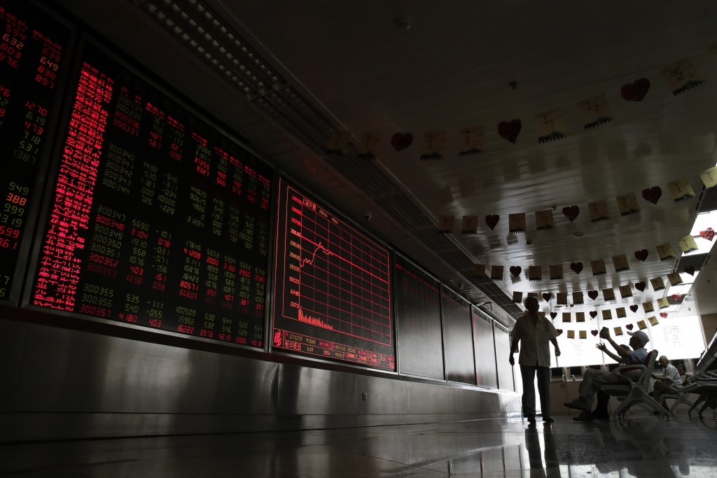 People react as they monitor stock prices at a brokerage house in Beijing, Thursday, Aug. 16, 2018. Asian shares are falling as investors fret over sl...
