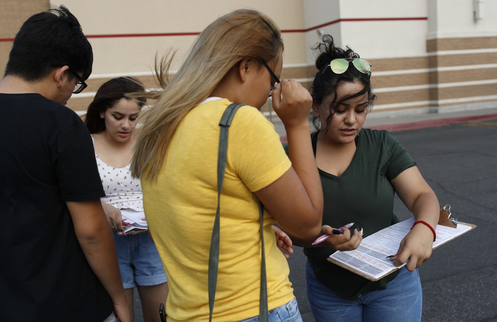 In this Aug. 15, 2018, photo, Maria Nieto, right, and Alma Romo, second from left, register people to vote in Las Vegas. Democrats in Nevada are worki...