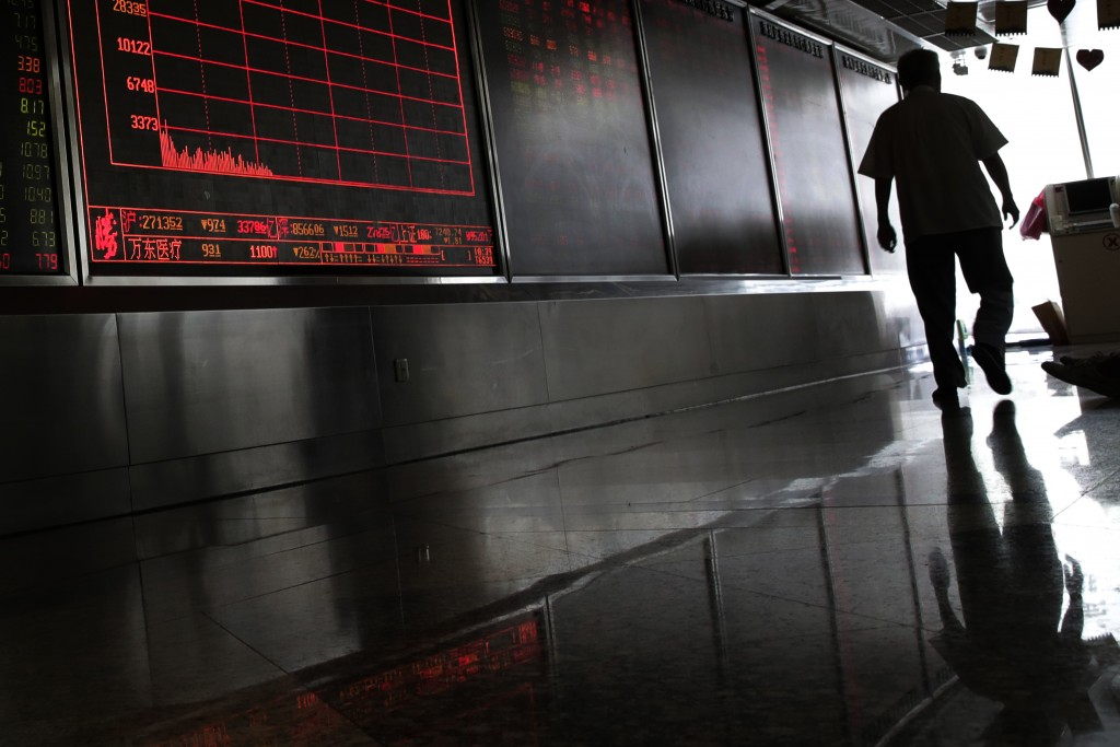 A man walks by an electronic board displaying stock prices at a brokerage house in Beijing, Thursday, Aug. 16, 2018. Asian shares are falling as inves...