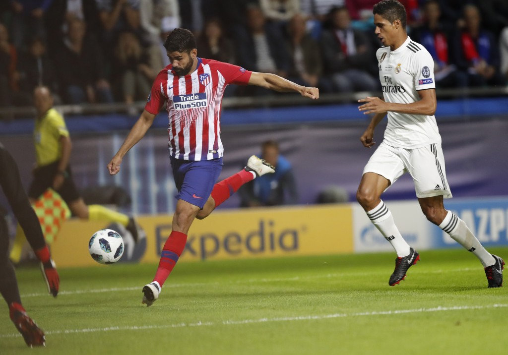Real Madrid's Raphael Varene, right, fails to stop Atletico's Diego Costa, left, from scoring his sides first goal during the UEFA Super Cup final soc...