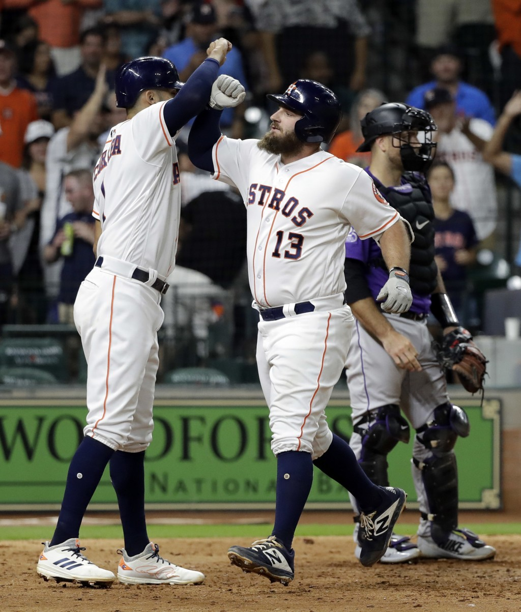 Houston Astros' Tyler White (13) celebrates with Carlos Correa after both scored on White's home run against the Colorado Rockies during the seventh i...