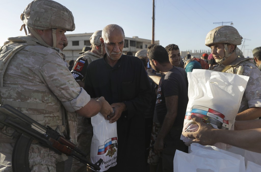 Local residents receive humanitarian aid from the Russian military in the town of Al-Rastan, Syria, Wednesday, Aug. 15, 2018. The Russian Defense Mini...