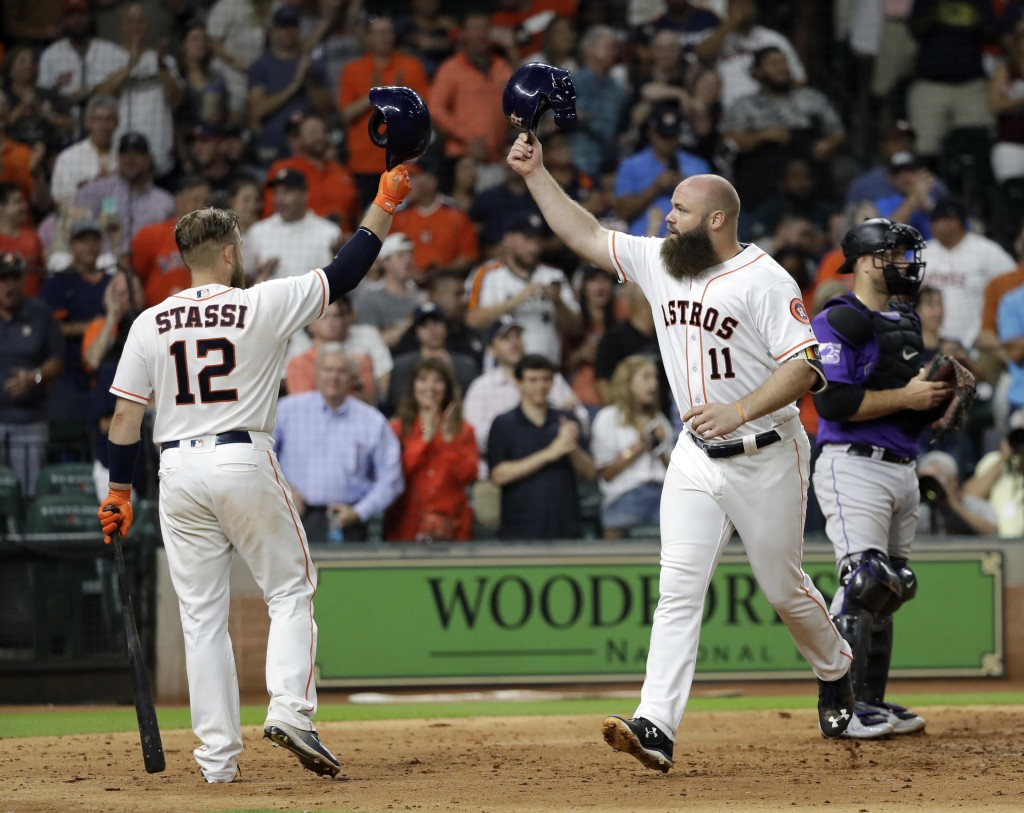 Houston Astros' Evan Gattis (11) celebrates with Max Stassi (12) after hitting a home run during the fifth inning of a baseball game against the Color...