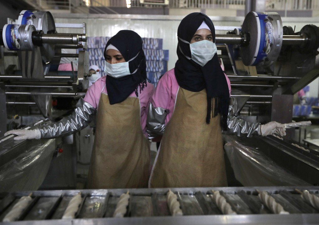 Workers produce ice creams on the assembly line at a factory in the city of Adra, Syria, Wednesday, Aug. 15, 2018. The Russian Defense Ministry said W...
