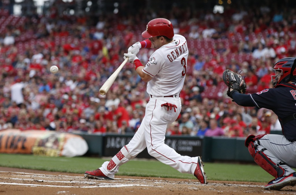 Cincinnati Reds' Scooter Gennett hits an RBI single off Cleveland Indians starting pitcher Shane Bieber during the first inning of a baseball game Wed...