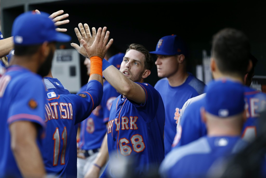 New York Mets' Jeff McNeil, center, high-fives teammates in the dugout after scoring on Todd Frazier's single during the first inning of a baseball ga...