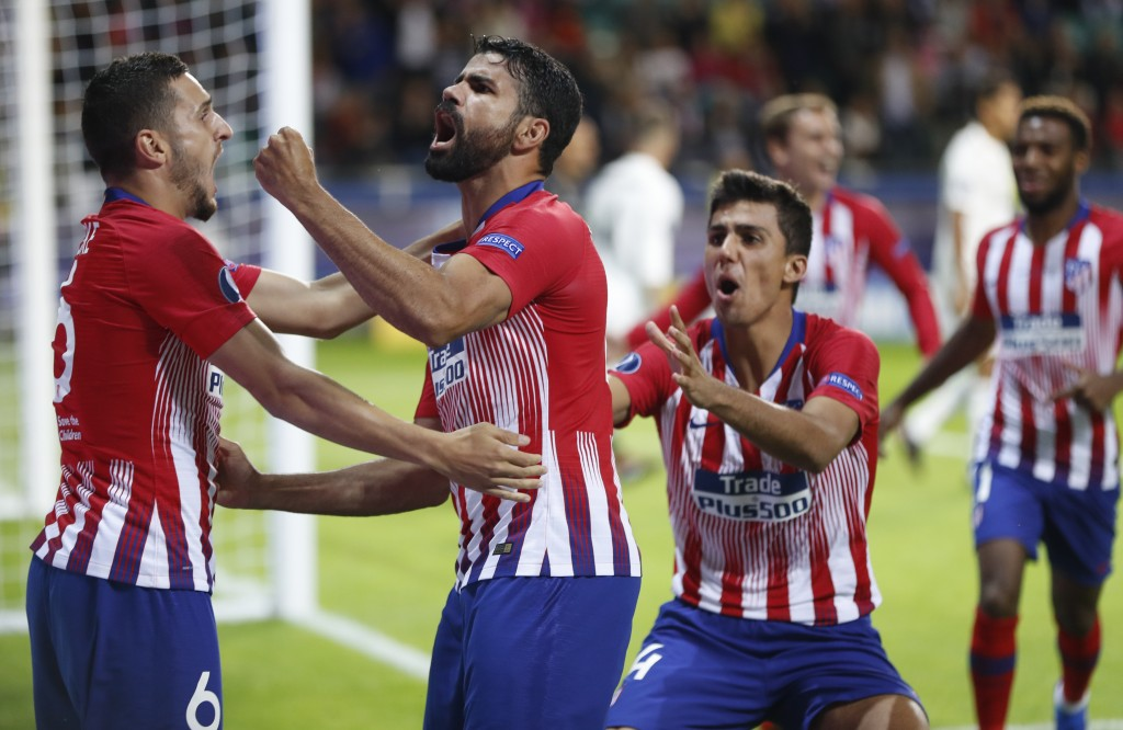 Atletico's Diego Costa, 2nd left celebrates with teammates after scoring his sides first goal during the UEFA Super Cup final soccer match between Rea...