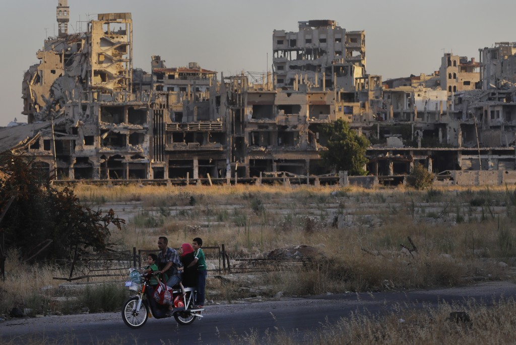 People ride their motorcycle by damaged buildings in the old town of Homs, Syria, Wednesday, Aug. 15, 2018. The Russian Defense Ministry said Wednesda...