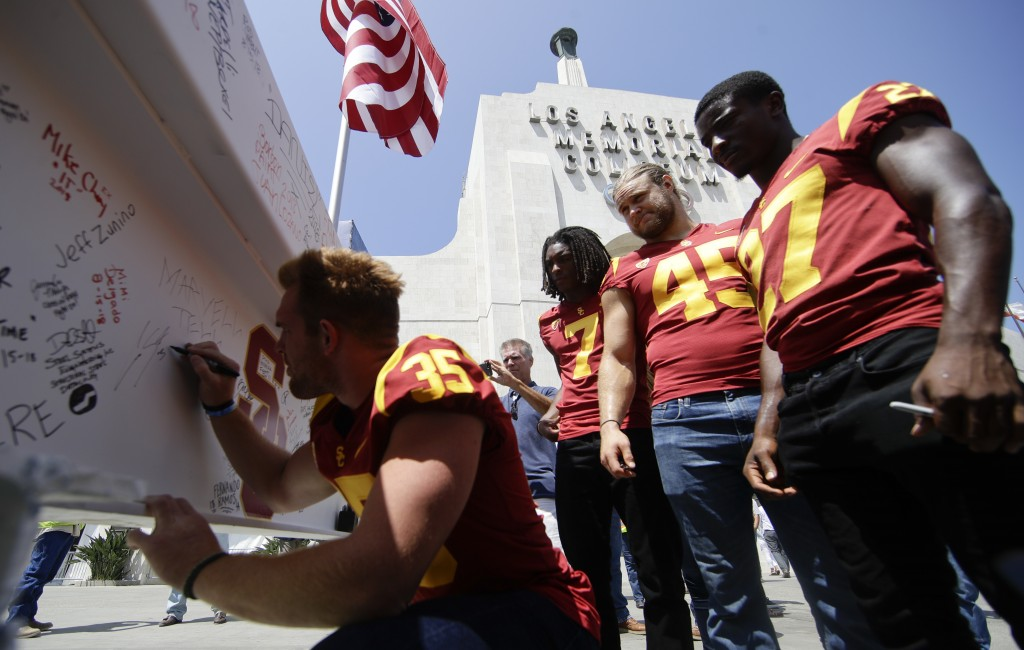 University of Southern California linebacker Cameron Smith signs the final beam, as other players look on, in front of the Los Angeles Memorial Colise...