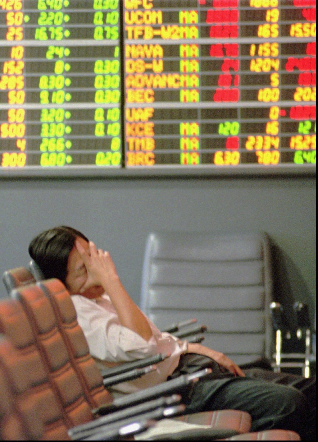 FILE- In this Nov. 21, 1997, file photo a Thai stock investor falls asleep while lonely monitoring a trading board at a stock house in the Stock Excha...