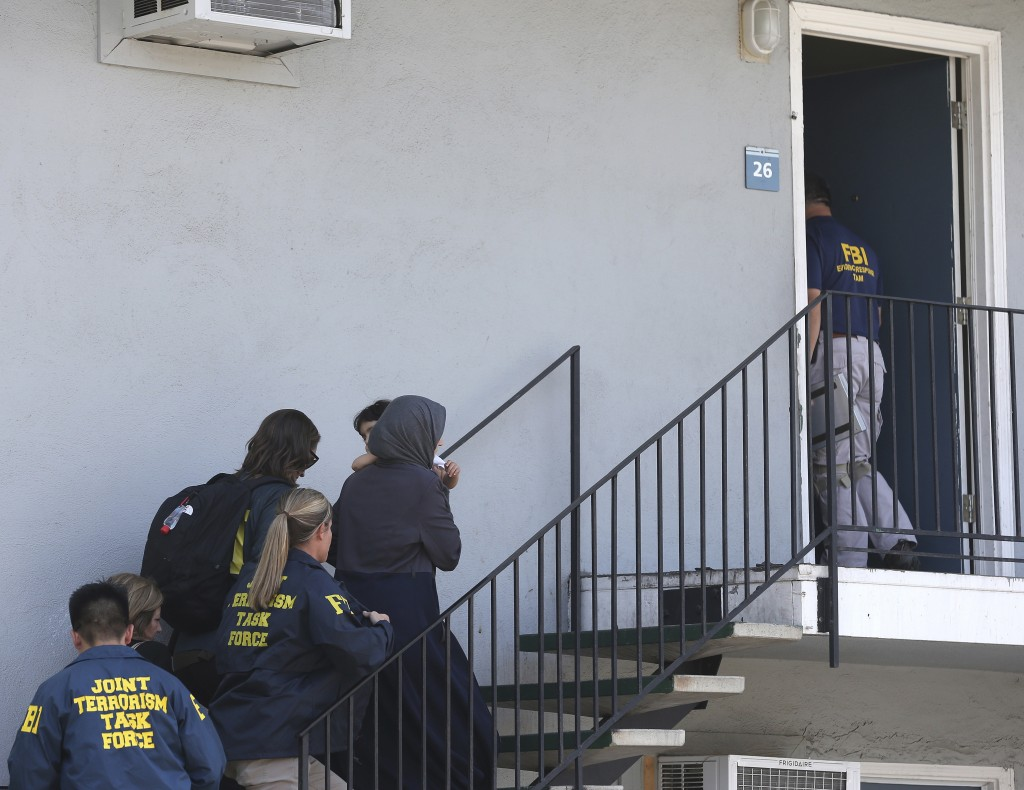 A woman carrying a child is escorted by authorities to an apartment following the arrest of a 45-year-old Iraqi refugee, Omar Ameen, Wednesday, Aug. 1...