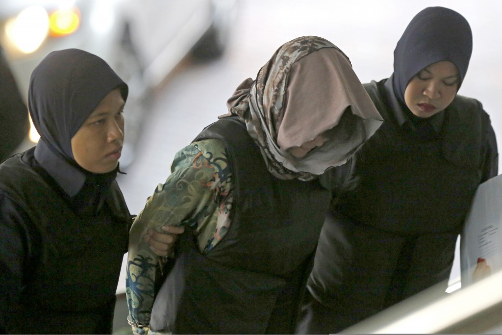 Vietnamese Doan Thi Huong, center, is escorted by police as she arrives for a court hearing at Shah Alam High Court in Kuala Lumpur, Malaysia, Thursda