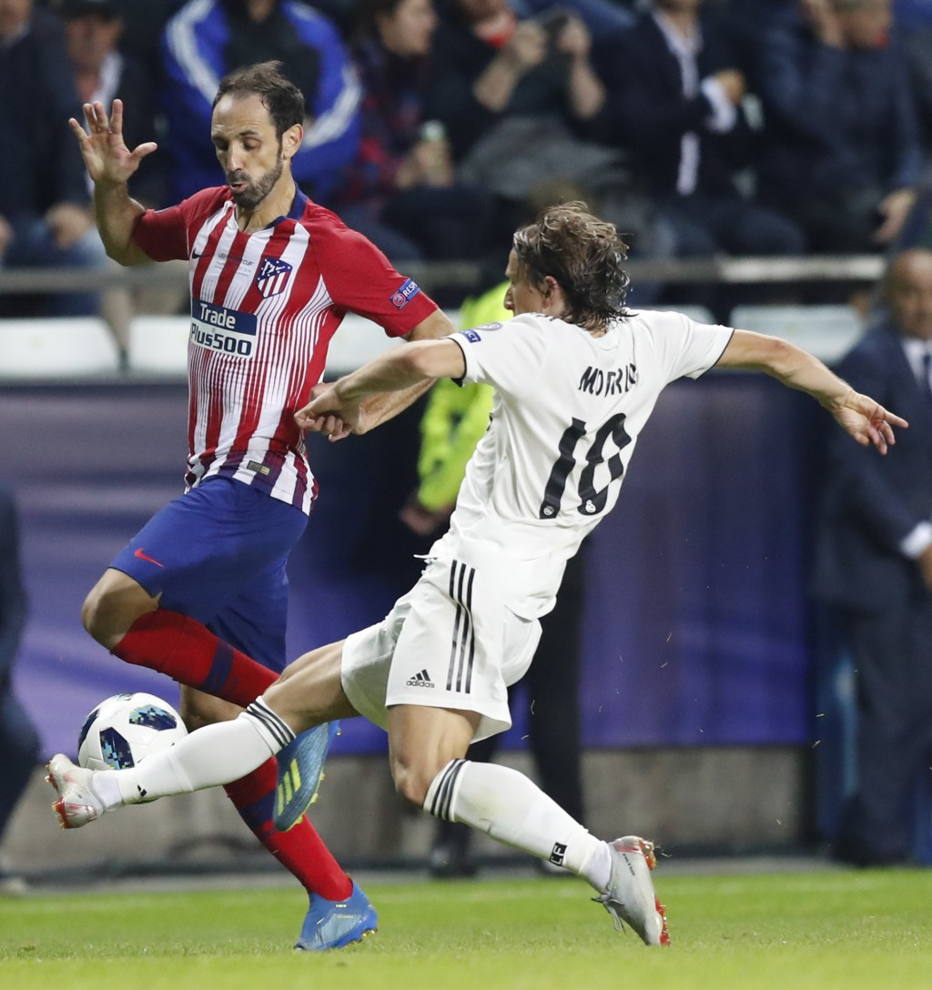 Real Madrid's Luka Modric, right, challenges Atletico's Juanfran, left, during the UEFA Super Cup final soccer match between Real Madrid and Atletico ...