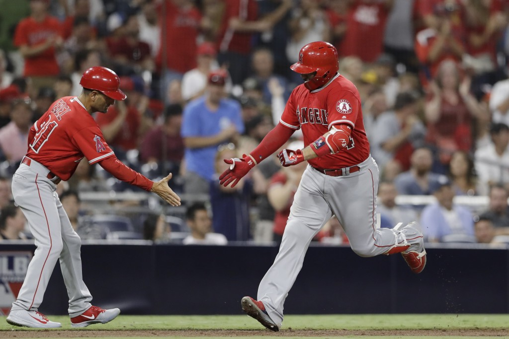 Los Angeles Angels' Rene Rivera, right, is greeted by third base coach Dino Ebel after hitting a home run during the ninth inning of a baseball game a...